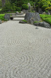 Zen garden. With stone bridge showing white gravel carefully raked to simulate ripples of water or symbolise space Stock Image