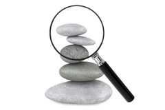 Zen garden stones and magnifying glass. On a white background Royalty Free Stock Photo