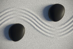 Zen garden in a top view with stones separated by a wave. Zen garden on sand with two black stones separated by a drawing ripples Royalty Free Stock Photos