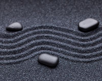 Zen garden with a wave lines in the sand with relaxing stones Stock Image