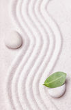 Zen garden with a wave lines in the sand with a relaxing white stone Stock Image