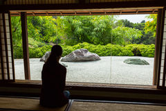 Zen garden. Woman looking through a window at a Japanese Zen Rock Garden Stock Images