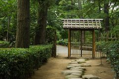 Zen gate and path. Japanese gate and stone path leading to a traditional japanese garden Royalty Free Stock Photo