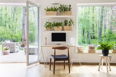Zen home office with computer in a beautiful, spacious living room interior with plants and an outside view through big windows stock photography