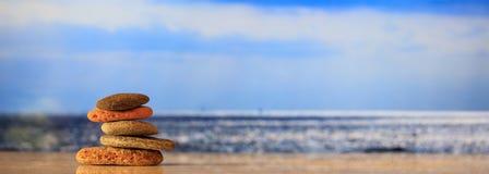 Zen kamieni sterta na niebieskiego nieba i morza tle Zdjęcia Royalty Free