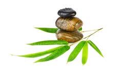 Zen kamienie z bambusowymi liśćmi odizolowywającymi na bielu Fotografia Royalty Free