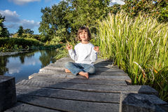 Zen kid doing yoga closing eyes for relaxation and mindfulness. Zen beautiful young 5-year old kid doing yoga bare feet relaxing alone, closing eyes for Stock Photography