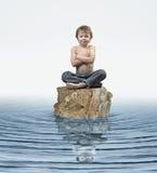 Zen Kid en roca en agua Fotos de archivo libres de regalías