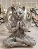 Zen Kitty Cat in Buddha Meditation Pose. Figure of a zen kitty cat in buddha meditation pose with another cat in the background royalty free stock photography