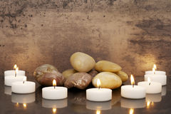 Zen-like candles. A circle of zen-like candles with a pile af rocks Royalty Free Stock Photography