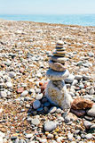 A zen-like grouping of stones. Zen stones stacked at beach against a gravel, sky and sea background Royalty Free Stock Images