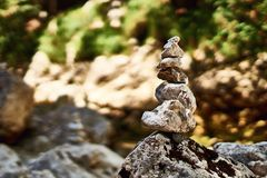 Pyramid of zen stones on the rocky mountains stream shore Royalty Free Stock Image