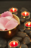 Zen-like rose petals. A wooden bowl with rose petals surrounded with candles and black stones in a zen-like atmosphere Royalty Free Stock Images