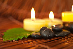 Zen-like SPA. Zen-like stones with water drops and green leafs Royalty Free Stock Images