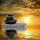 Zen massage stones at sunset reflected in water Stock Images