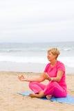 Zen meditation. Senior woman doing zen meditation on beach Stock Photo