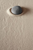 Zen meditation stone purity well being. Zen meditation stone relaxation or concentration point to focus and to meditate round grey rock in dry sand simplicity Royalty Free Stock Image