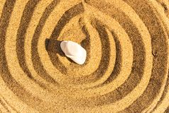 Zen meditation stone in sand, concept for purity harmony and spi Royalty Free Stock Photo