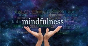 Zen Mindfulness Meditation. Female hands reaching up towards the word 'Mindfulness' floating above surrounded by a relevant word cloud on a dark blue night sky Royalty Free Stock Image