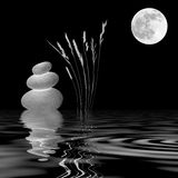 Zen Moonlight. Zen abstract of three natural grey pebbles, wild grasses and a full moon with reflection over rippled water. Over black background Royalty Free Stock Images