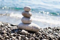 Zen overzeese die stenenkiezelstenen in een piramide op overzeese kust worden gestapeld stock afbeelding