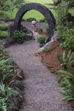 Zen Path. A curved pebble walkway leads through a stone circle to a curved path maze with a large stone sphere in the center. Other smaller spheres can be seen Stock Photos