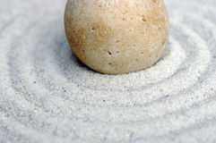 Zen pebble close-up 2. Raked sand around a pebble in a small tabletop rock garden Royalty Free Stock Photography