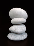 Zen Pebbles. A balanced stack of white pebbles against a black background Stock Photo