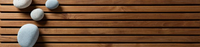 Zen pebbles set on design wooden board, top view banner royalty free stock image