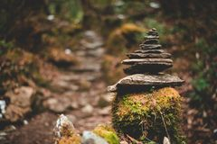 Zen pile of rocks in balance in a forest. Zen pile of flat rusty rocks in balance on top a grass covered piece of wood in an autumn forest royalty free stock photo