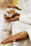 Zen practise. A group of indian man and woman practise karate zen together, focus on first hand royalty free stock image