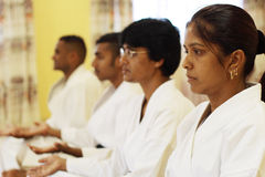 Zen practise. A group of indian man and woman practise karate zen together, focus on first hand stock photos