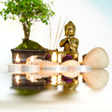Zen Reflections. A small zen altar surrounded by candles and bonsai, is reflected in water Stock Image
