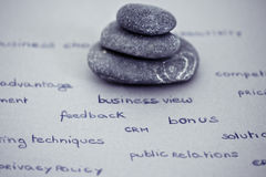 Zen and relax in the business environment. Zen stones stacked surrounded by business words Royalty Free Stock Images