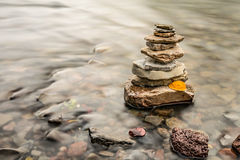 Zen Rock Cairn. Long exposure of water flowing around rock cairn in stream with fallen autumn leaf on it royalty free stock photos