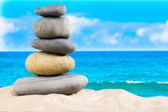 Zen rock, concept of harmony and balance. Zen stones pyramid on the beach with amazing turquoise blue water sea and sky.  royalty free stock photography