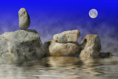 Zen rock sits alone under the moon Stock Photo