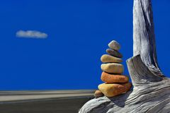 Zen rock tower at beach on log Stock Photography