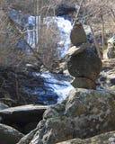 Zen Rocks Stand Before a Waterfall. Rocks stacked for tranquility and zen stand before a waterfall at Lower Whiteoak Falls Royalty Free Stock Photos