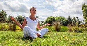 Zen 20s blond dziewczyna medytuje w zielonych surrondings Obraz Royalty Free