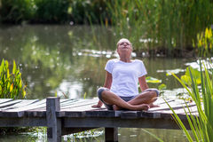 Zen 20s blond girl breathing, pond environment Stock Image