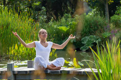 Zen 20s blond girl enjoying,water environment. Outdoors meditation - smiling young yoga woman in lotus pose,relaxing and meditating on a wooden path with green Stock Photography