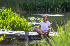 Zen 20s blond girl meditating, pond environment Stock Images