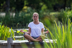 Zen 20s blond girl thinking, pond environment Royalty Free Stock Image