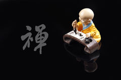 Zen's realm. A Chinese monk sitting by a stone table and painting his mind the realm of Zen. Zen in the heart,Zen in the painting. Chinese character in black royalty free stock photo