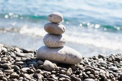 Zen sea stones pebbles stacked in a pyramid on sea coast stock image