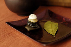 Zen Spa. Stone cairn and a leaf in warm colors Stock Images