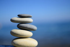 Zen spa stones with blue water and sky. Balanced stones background, copy space. Spa symbol. Balancing stones. Symbol of stability. Tranquil, relaxation and stock photo