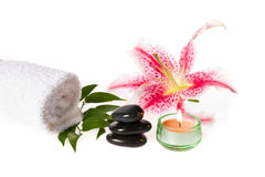 Zen spa stones and lily. Zen spa with candle, towel, zen stones and lily on white background Royalty Free Stock Photo