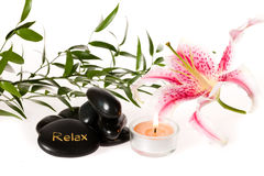 Zen spa stones and lily. Zen spa with candle, zen stones and lily on white background Royalty Free Stock Photo